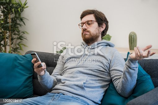 824614192 istock photo Annoyed frustrated male reading bad news on the cellphone 1203019417