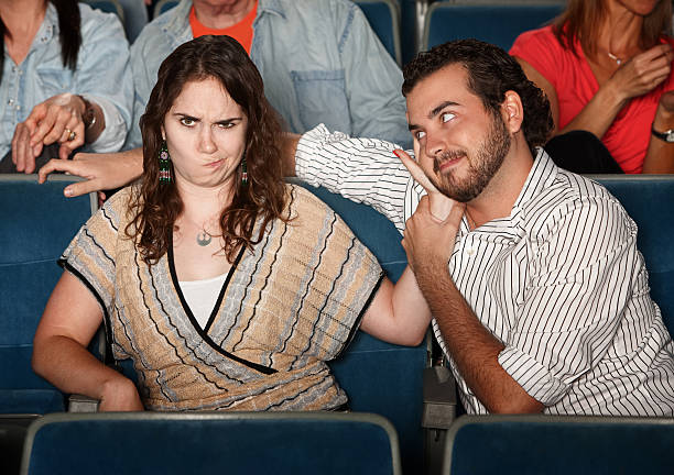 Annoyed Girlfriend In Theater Girlfriend annoyed with rude man in theater bad date stock pictures, royalty-free photos & images