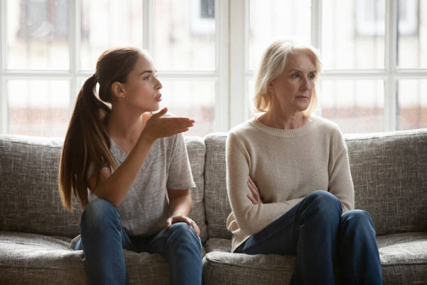 Annoyed grown up daughter expressing complaints to elderly mother Annoyed grown up daughter expressing complaints to elderly mother annoyed females sit on couch, old stubborn mom dont want make concessions, different ages, generational gap, family conflict concept arguing stock pictures, royalty-free photos & images