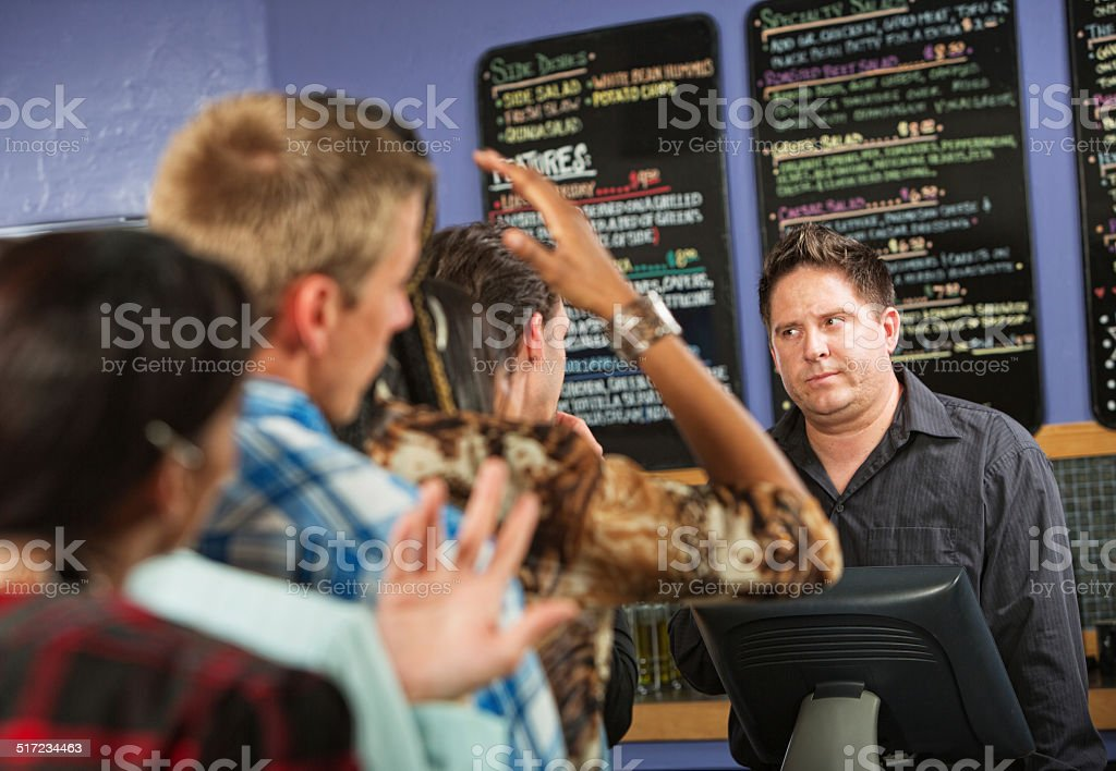 Annoyed Male Cafe Worker Annoyed male cafe worker with long line Adult Stock Photo