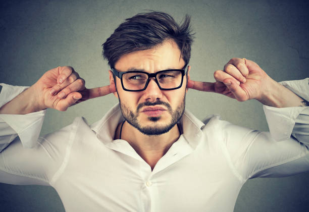 Annoyed man covering ears stock photo