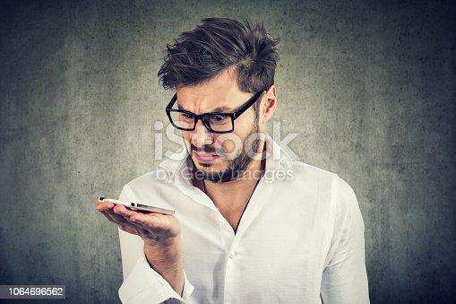 824614192istockphoto Annoyed man holding smartphone on hand 1064696562