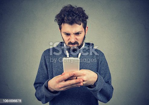 824614192istockphoto Annoyed man looking with anger at smartphone 1064696678