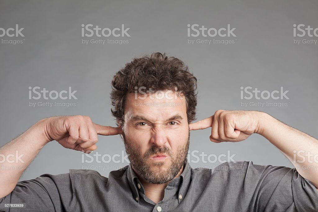 Annoyed mature man plugging ears with fingers stock photo