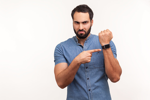 Annoyed punctual man with beard in blue shirt pointing finger at wrist watch mock up display and expressing dissatisfaction with late time, deadline. Indoor studio shot isolated on white background