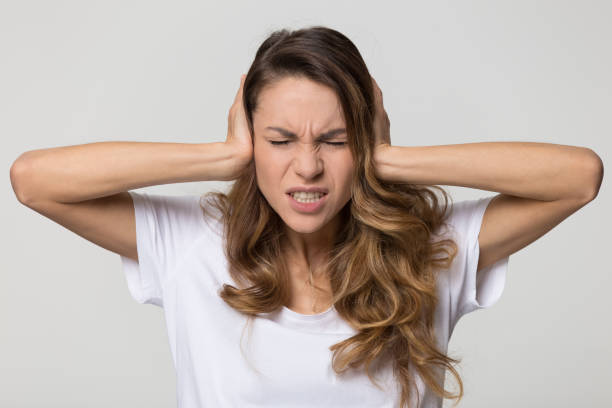 Annoyed stressed woman covering ears with hands feeling ear pain Annoyed stressed woman cover ears feel hurt ear ache pain otitis suffer from loud noise sound headache, irritated stubborn girl deaf hear not listen to noisy music isolated on white studio background ignoring stock pictures, royalty-free photos & images