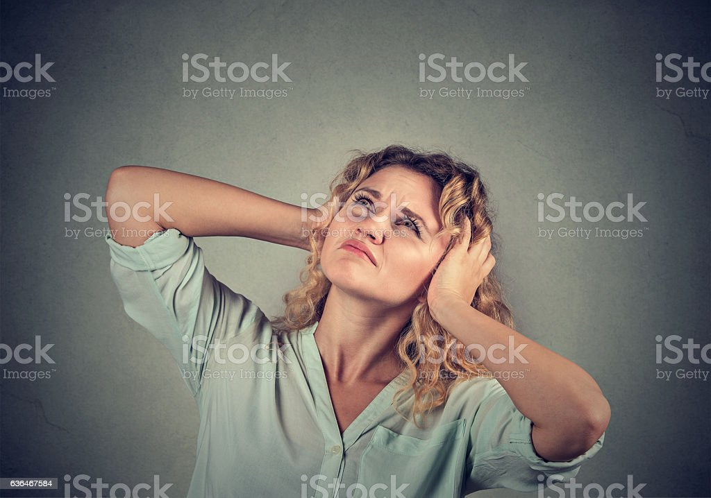 annoyed stressed woman covering ears with hands looking up stock photo