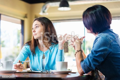 Annoyed teen girl talking to mother in coffee shop
