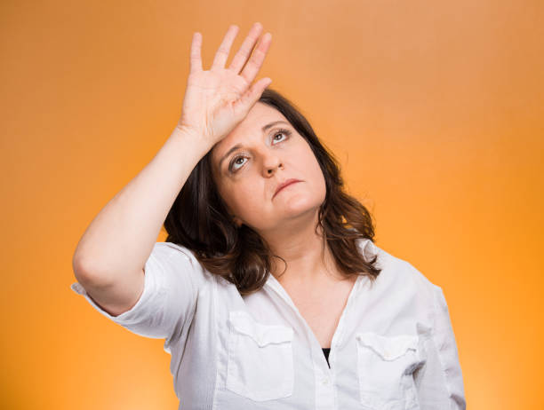 annoyed tired middle aged woman placing back hand on forehead Closeup portrait annoyed tired middle aged woman placing back hand on forehead, tragedy of it all, woe is me, exaggerating isolated orange background. Negative emotion, facial expression, perception diva human role stock pictures, royalty-free photos & images