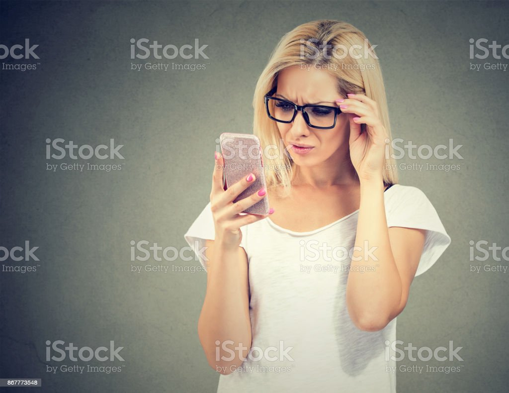 Annoyed upset woman in glasses looking at her smart phone with frustration stock photo