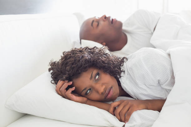 Annoyed woman lying in bed with snoring boyfriend stock photo