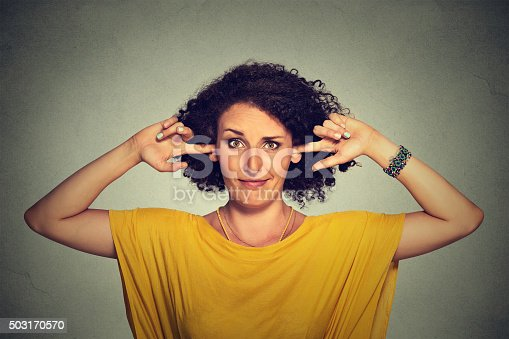 istock Annoyed woman plugging ears with fingers doesn't want to listen 503170570