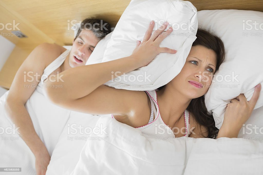 Annoyed woman trying to block out partners snoring royalty-free stock photo