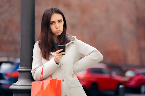 Annoyed Woman with Smartphone and Shopping Bag