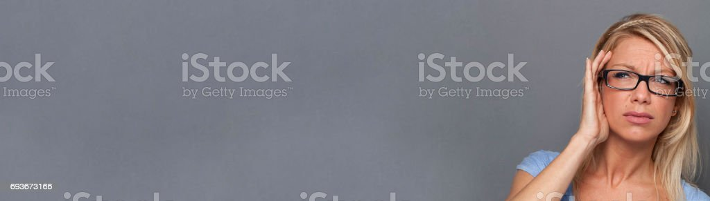 annoyed young blond woman looking bothered, suffering from headache, banner stock photo