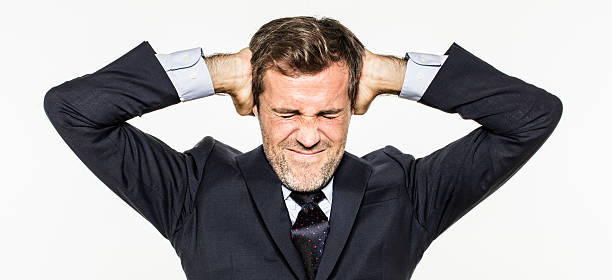 annoyed young business man covering his ears from corporate burnout - covering ears stock photos and pictures