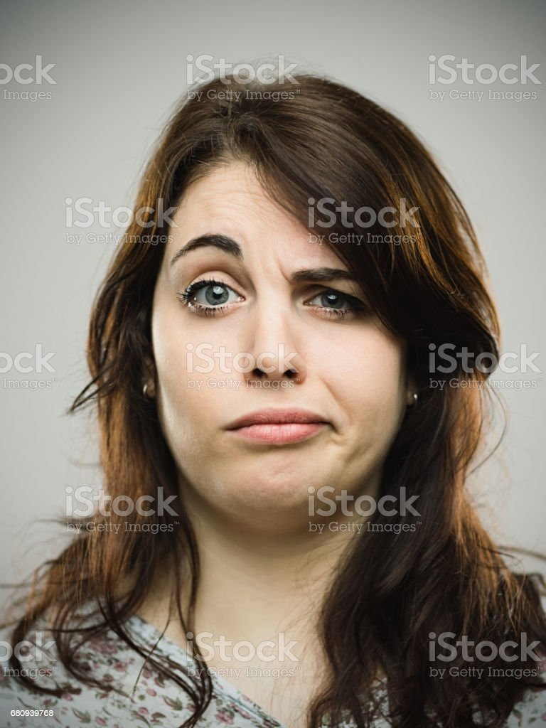 Annoyed young female against gray background stock photo