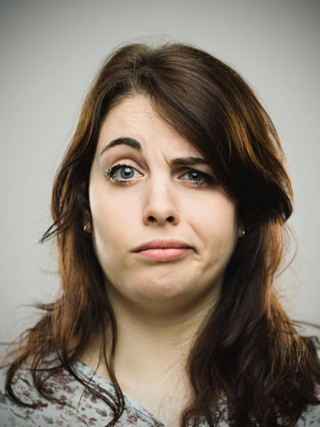 annoyed young female against gray background - frowning stock photos and pictures