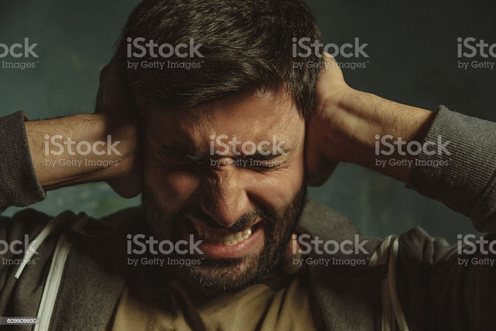 Annoyed young man closing ear with hand stock photo