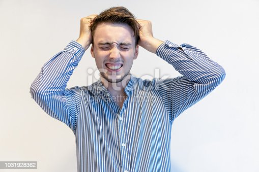 1162960006istockphoto Annoyed young man feeling despair and holding head in hands 1031928362