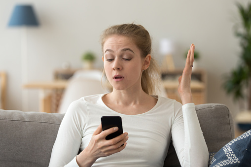 istock Annoyed young woman looking at smartphone having problem with phone 1124667612