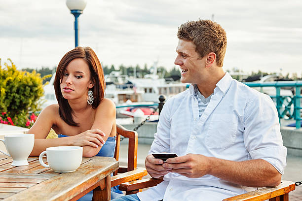 Annoying Boyfriend with Smart Phone Photo a young couple having a disasterous date.  Young woman looks annoyed as her date seems more excited about his phone than he is about being with her. bad date stock pictures, royalty-free photos & images