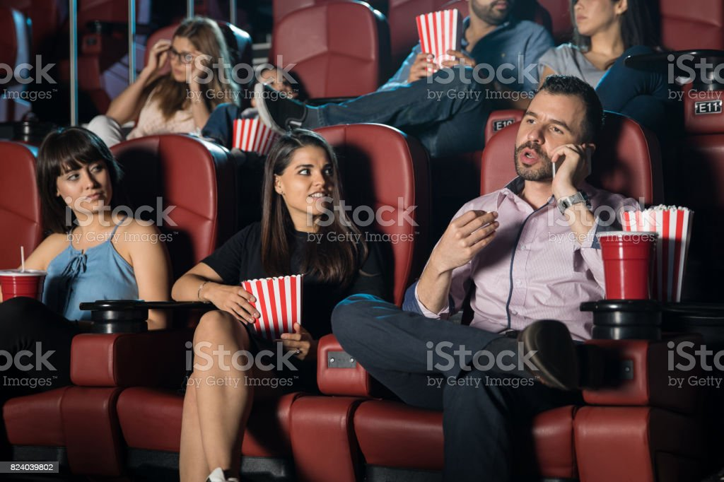Annoying man at the movie theater stock photo
