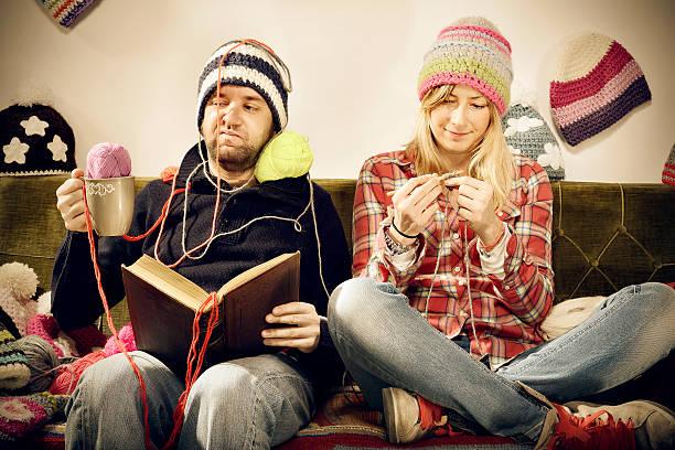fastidiose knitter ritratto di donna giovane coppia sul divano - lavorare a maglia foto e immagini stock