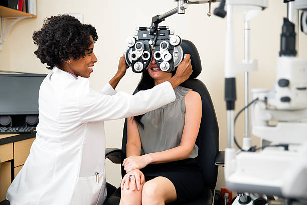 annual eye exam by optometrist - optometrist stock pictures, royalty-free photos & images