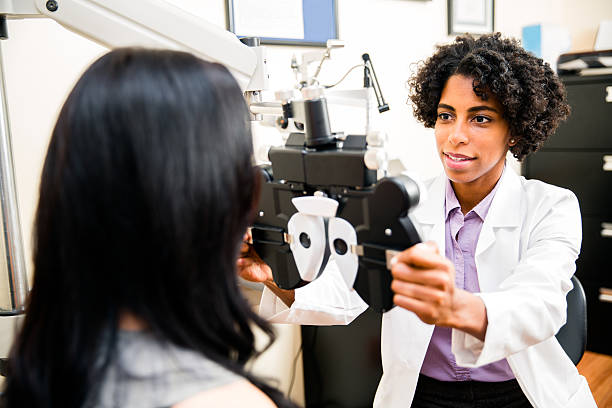 annual eye exam by the optometrist - optometrist stock pictures, royalty-free photos & images