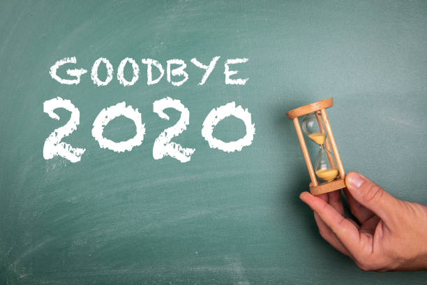 GOODBYE 2020. Annual report, new year's expectations, planning and goals concept. Sandglass in hand stock photo