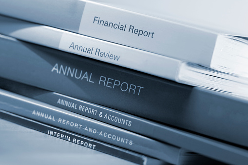 A blue toned close up image of a loosely arranged stack of thick generic business annual financial annual and accounts.  The reports are arranged on a wooden table and shot with a shallow depth of field.