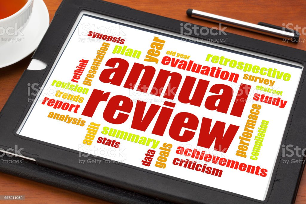 annual review word cloud on tablet stock photo