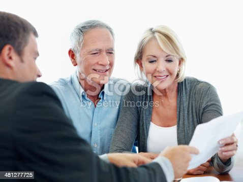 A friendly financial broker showing a senior couple a document