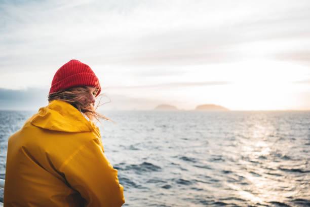 Ein einmanniger Reisender, der auf einem Schiff schwebt und nach Sturm und nebligen Bergen auf der Skyline auf Dasstal schaut. Lifestyle-Reisen outdoor skandinavische authentische Landschaft, Fernweh – Foto