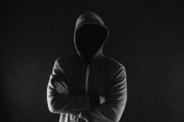 Anonym und gesichtslos Mann unter Hoodie mit verschränkten Armen isoliert auf dunklem Hintergrund - inkognito und geheimnisvollen Verbrecher auf Internet-Aktivitäten-Konzept. – Foto