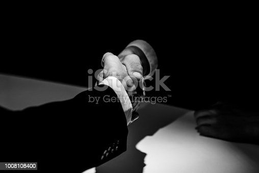 Black and white tone of anonymous business partners making handshake in dark shadow