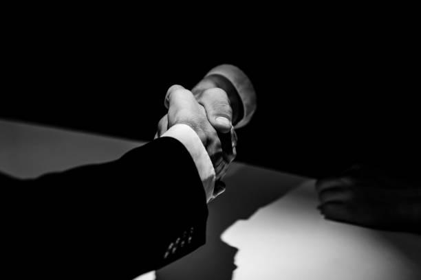 シャドウのハンドシェイクを行う匿名ビジネス パートナー - 腐敗 ストックフォトと画像