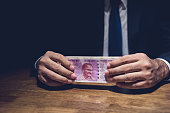istock Anonymous businessman holding money, Indian Rupee currency, at the table in dark private room 876037398