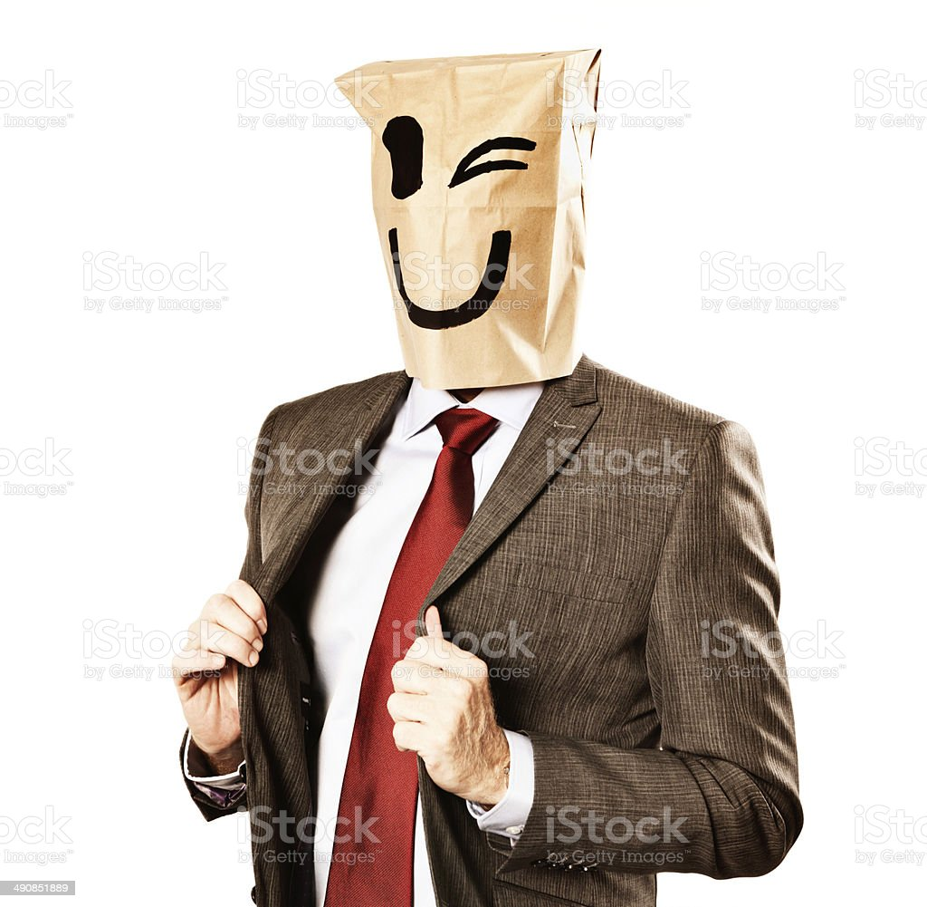 Anonymous businessman in winking paper-bag mask holds jacket lapels proudly stock photo
