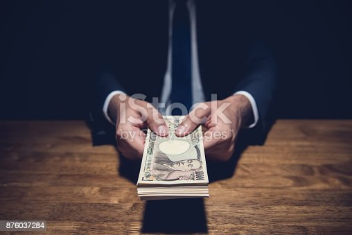 istock Anonymous businessman secretly giving away money, Japanese Yen currency, in private dark room 876037284