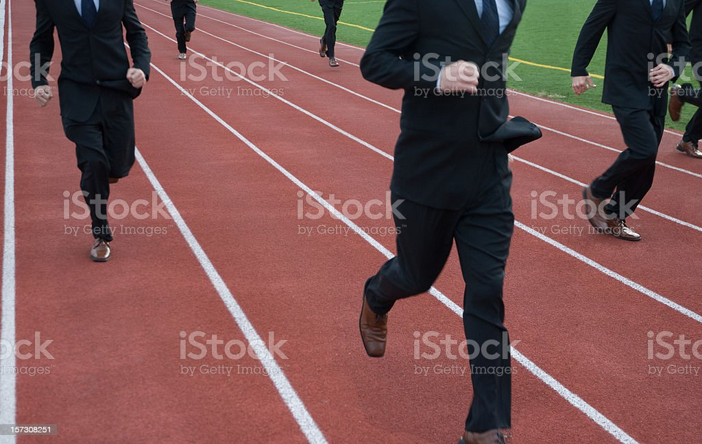 Anonymous Businessmen Run a Race on Running Track stock photo