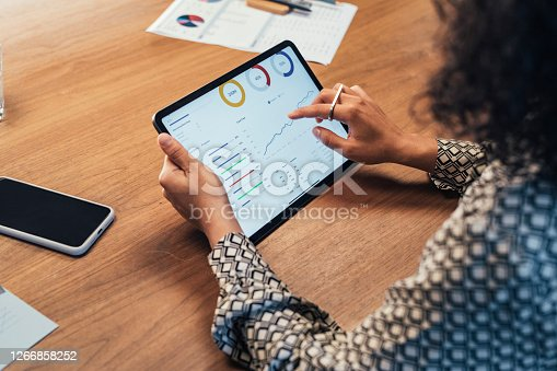 istock Anonymous Businesswoman Analyzing Statistical Business Reports on her Tablet PC at the Office, a Close Up 1266858252