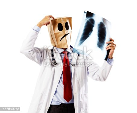 An anonymous man disguised in a paper-bag mask, probably a doctor, examines an X-ray, looking completely mystiified.  Not the image of a competent professional man!