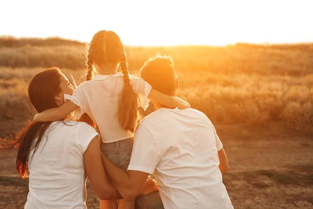 Anonymous family admiring sunset stock photo