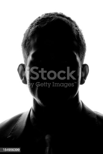 Silhouette of a young man looking looking at the camera.