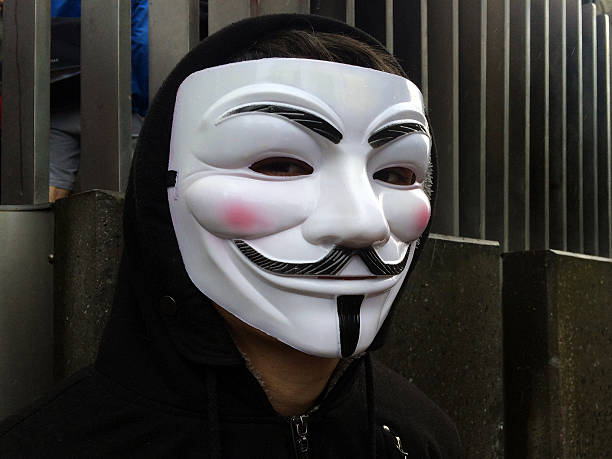 anonymous group member wearing guy fawkes mask - guy fawkes mask stock photos and pictures