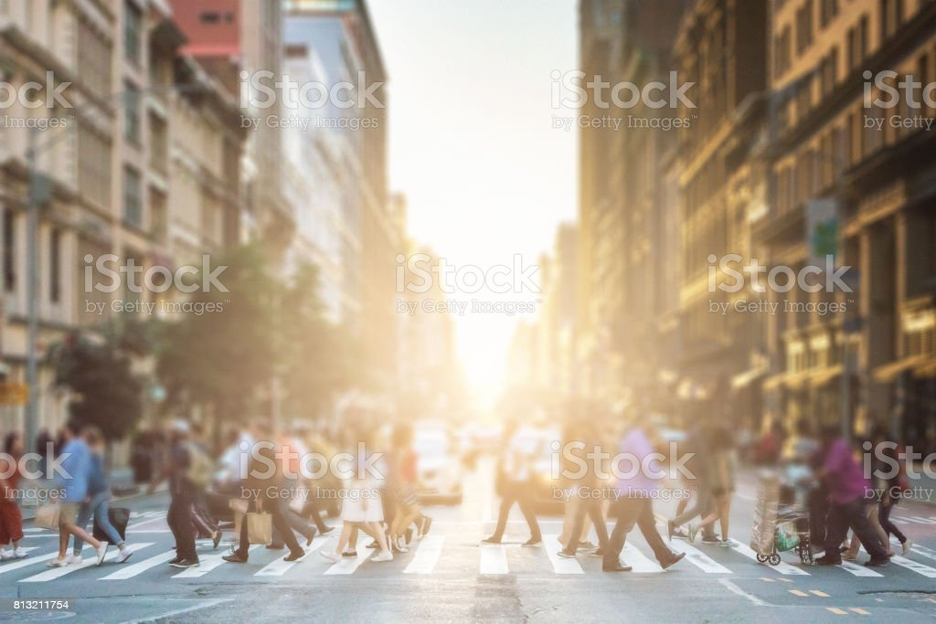 Anonymous group of people walking across a pedestrian crosswalk on a New York City street with a glowing sunset light shining in the background