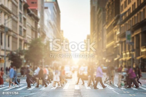813211754 istock photo Anonymous group of people walking across a pedestrian crosswalk on a New York City street with a glowing sunset light shining in the background 813211754
