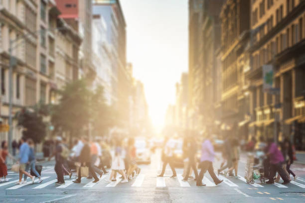 Anonymous group of people walking across a pedestrian crosswalk on a New York City street with a glowing sunset light shining in the background stock photo